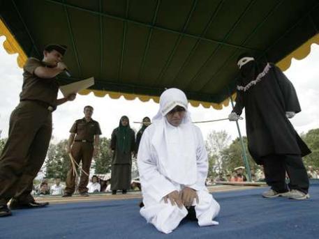 Schreckliches Foto aus Indonesien! Eine Frau kniet hilflos am Boden, hinter ihr der maskierte Scharia-Polizist mit seiner Peitsche. Vor 200 Menschen wird Irdayanti Mukhtar (34) gefoltert