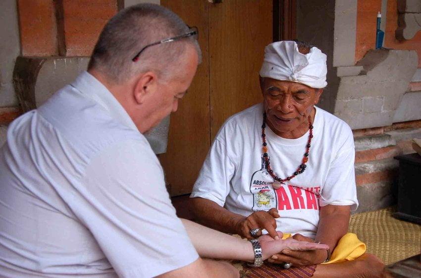 """Ketut Liyer: Der alte Mann liest einem Patienten, wie er seine Kunden nennt, aus der Hand - """"Sie werden 100 Jahre alt und bald reich!"""" Fotoquelle: spiegel.de"""
